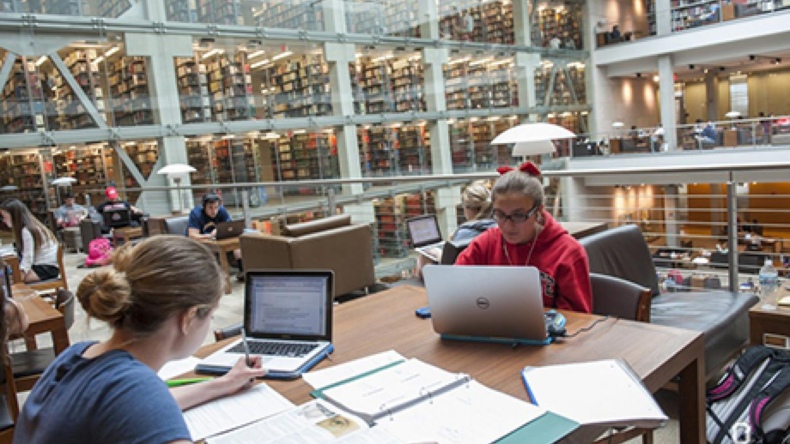 Students in front of columns of books in Thompson Hall Library
